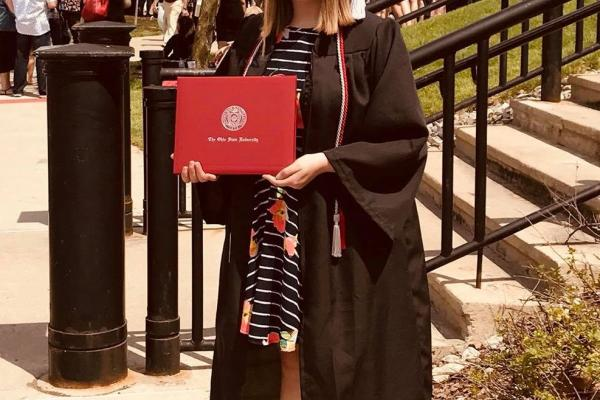 Taylor Brown holds her diploma and wears her graduation robes at 2018's spring commencement